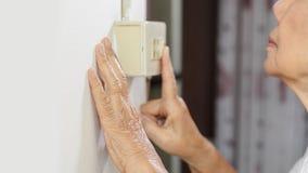 Mão idosa da mulher que gira sobre um interruptor da parede foto de stock