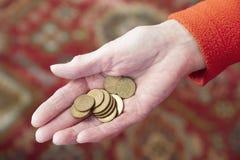 Mão idosa que guarda as economias de cobre da pensão das moedas de um centavo das moedas da mudança fraca do dinheiro do dinheiro imagem de stock