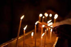 A mão ilumina uma vela na igreja Fotografia de Stock
