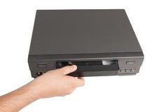 A mão introduz a fita de vídeo no videorecorder Imagens de Stock