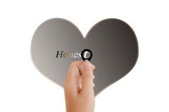 Mão isolada com a lente e o texto honestos com forma do coração no whit fotografia de stock