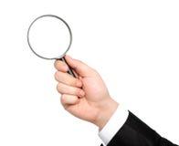 Mão isolada de um homem de negócios no terno guardarando glas de ampliação Imagem de Stock Royalty Free