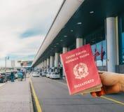 Mão isolada que guarda um passaporte italiano com fora do entranceway do aeroporto do foco Fotografia de Stock