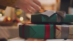 a mão 4K põe a caixa de presente envolvida sob a árvore de Natal video estoque