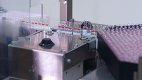 A mão leva embora duas ampolas médicas da linha de produção Planta farmacêutica video estoque