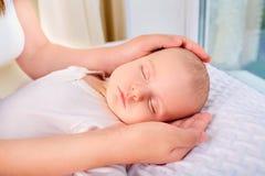 Mão loving da mamã que guarda a criança recém-nascida de sono bonito do bebê matriz Imagem de Stock