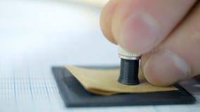 A mão macro da vista lateral brilha a lanterna elétrica no papel e na ferramenta video estoque