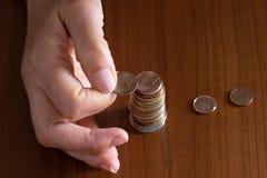 Mão madura da mulher que põe moedas em uma pilha sobre a tabela de madeira closeup Euro- moedas europeias, conceito da pobreza co foto de stock royalty free