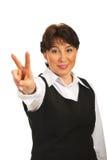 Mão madura do sinal da vitória da mostra da mulher fotos de stock