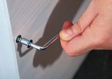 A mão mantém a mobília da chave de Allen introduzida na cabeça de parafuso. fotografia de stock