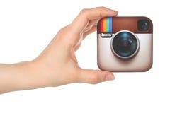 A mão mantém o logotipo de Instagram impresso no papel no fundo branco Fotografia de Stock Royalty Free