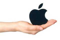 A mão mantém o logotype da maçã impresso no papel no fundo branco Foto de Stock Royalty Free