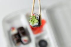 A mão mantém o rolo com hashis, rolos, sushi hashis, gengibre, molho de soja na entrega do recipiente Imagem de Stock