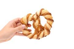 A mão mantem recentemente o pretzel extravagante cozido. Fotografia de Stock Royalty Free