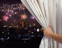 Mão masculina aberta a cortina de janela e para ver o fogo de artifício no fundo do céu da cidade da noite, conceito da celebraçã foto de stock