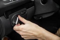 A mão masculina branca firma o interruptor do farol dentro do carro preto imagem de stock royalty free