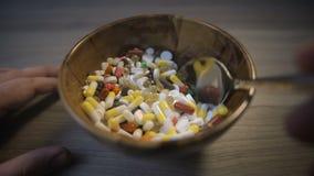 Mão masculina com uma colher que agita um grupo dos comprimidos O conceito de uma conspiração farmacêutica filme