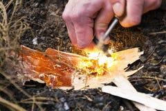 A mão masculina começa o fogo com aço do fogo do magnésio, grevista do fogo Fotos de Stock
