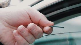 A mão masculina dá o cartão de memória do SD à janela de carro aberta da calha do motorista da mulher vídeos de arquivo
