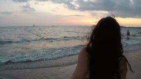 Mão masculina da posse da jovem mulher que anda na praia no ponto da câmera da ação do por do sol de Vew da menina de sorriso fel video estoque