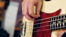 Mão masculina direita que joga a guitarra-baixo video estoque