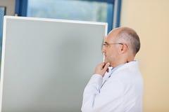 Mão masculina do doutor With em Chin Standing By Flipchart Imagens de Stock Royalty Free