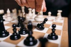 Mão masculina do jogador de xadrez que guarda a figura branca Imagens de Stock