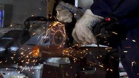 A mão masculina eliminou partes de tubulação de água com moedor de ângulo O corte de um aço com espirra das faíscas na construção video estoque