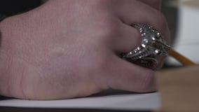 A mão masculina grande com anel de prata maciço no desenho do dedo no papel vazio usando o lápis Brown de madeira vídeos de arquivo