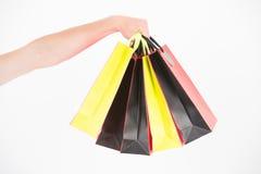 A mão masculina guarda cinco sacos de compras Conceito da compra A mão guarda o grupo de sacos de compras coloridos Compra no pre Fotografia de Stock Royalty Free