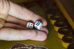 A mão masculina guarda dados no jogo da gamão fotografia de stock royalty free