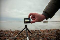 A mão masculina inclui a câmera da ação, olhar marinho do tiro Imagens de Stock Royalty Free