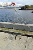 A mão masculina mantém uma armadilha feito a si próprio para caranguejos contra o mar de Barents Imagem de Stock