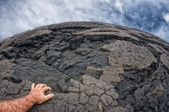 Mão masculina na costa preta havaiana da lava Fotos de Stock Royalty Free