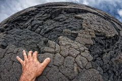 Mão masculina na costa preta havaiana da lava Fotografia de Stock Royalty Free