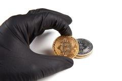 A mão masculina na luva preta mantém o bitcoin isolado no branco Conceito do crime e do cryptocurrency foto de stock
