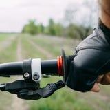 Mão masculina na luva que guarda o guiador da bicicleta Fotos de Stock