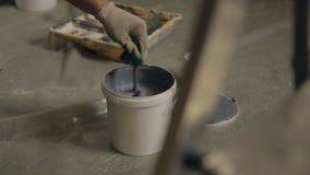 Mão masculina na varinha da agitação da luva, pintura cinzenta em um frasco, em um assoalho concreto video estoque