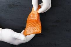 Mão masculina nas luvas que guardam uma parte fresca orgânica de salmões imagem de stock