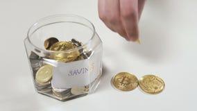 A mão masculina põe os bitcoins dentro de um frasco de vidro com economias vídeos de arquivo