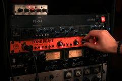 Mão masculina que ajusta o botão no instrumento imagem de stock