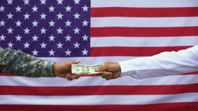 Mão masculina que dá o dinheiro ao soldado, pagamento do salário, corrupção militar, benefícios video estoque
