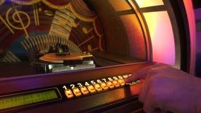 Mão masculina que empurra botões para jogar a música na caixa musical velha, selecionando registros vídeos de arquivo