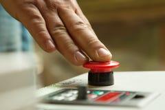 Mão masculina que empurra o botão de parada da emergência Foto de Stock