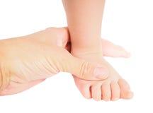 Mão masculina que guarda firmemente em torno de um pé da criança isolada fotografia de stock