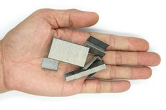 Mão masculina que guarda grampos do metal para o grampeador isolado no fundo branco imagens de stock royalty free