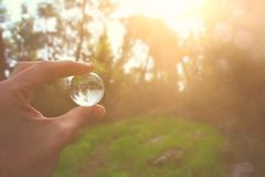 mão masculina que guarda o globo de cristal pequeno curso e conceito global das edições imagem de stock