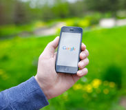 Mão masculina que guarda o iPhone com Google na tela Fotos de Stock