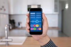 Mão masculina que guarda o telefone com a casa home esperta da cozinha do app foto de stock