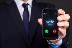 Mão masculina que guarda o telefone esperto com chamada entrante da esposa fotografia de stock royalty free